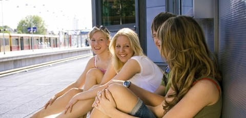 Teenagers sitting on a train station platform